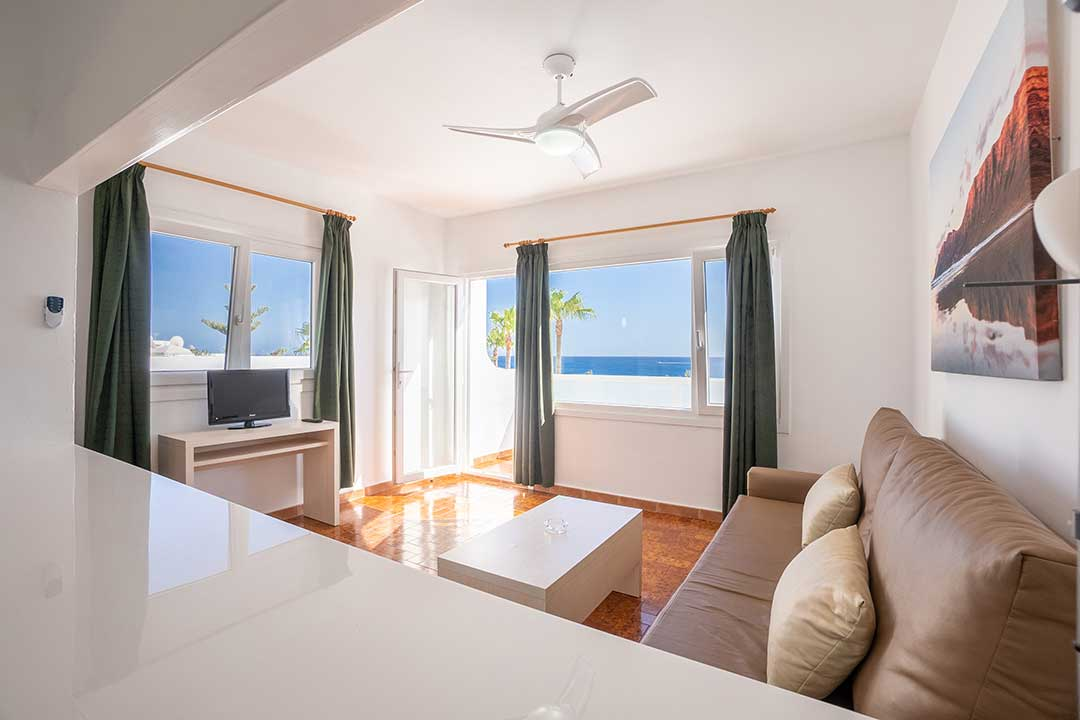Panoramic view of living room with window overlooking the sea.